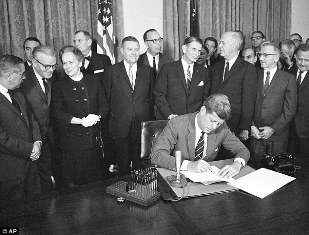President John F. Kennedy signs a bill authorizing $329 million for mental health programs at the White House in Washington.  Image courtesy of Associated Press.