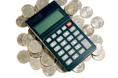 image of calculator resting on pile of coins