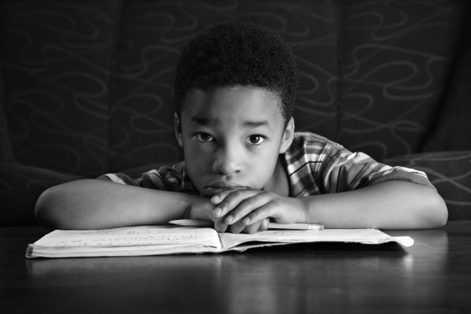 Young African American boy sits on the floor at a coffee table. He is looking towards the camera with his homework on the table. Horizontal shot.